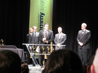 "Jim Distasio accepts a Midwest Emmy for the documentary ""5000 Miles From Home"" as fellow honoree Paul Basile (right) looks on with pride."